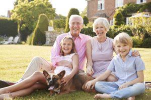 Grandparents and grandchildren sitting in garden with dog